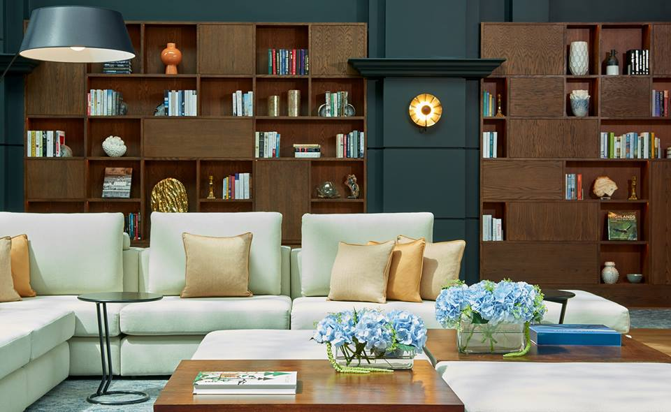 An image of the library at Fairmont St Andrews. Plush sofas in front of dark wood shelving unit containing books and ornaments.