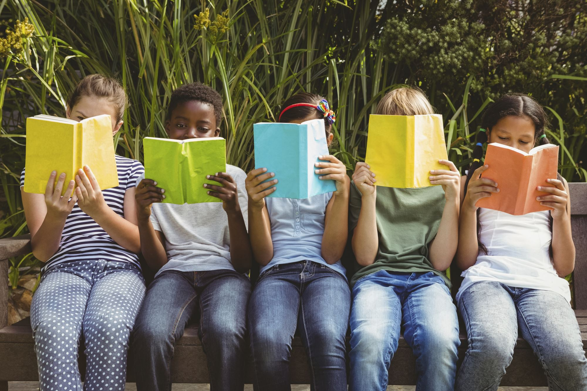 An image of children reading, sat in front of greenery.
