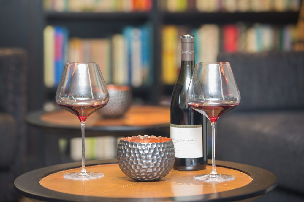 A photograph os two wine glasses, a wine bottle, and a candle on a small table in front of a blurred bookcase.