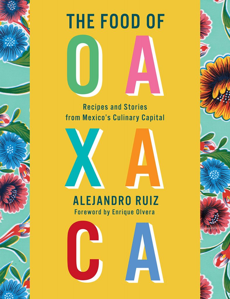 The cover of the cookbook 'The Food of Oaxaca' by Alejandor Ruiz. The title is multicoloured text on yellow background. This is bordered at either side by floral designs on a turquoise background.