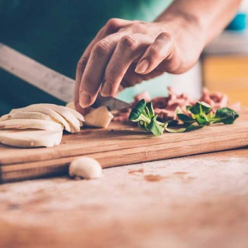 A photograph of someone cutting mushrooms and herbs on a chopping board.