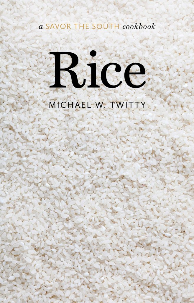 The cover for the cookbook 'Rice' by Michael W. Twitty. Featuring the title as black text on a background image of rice.