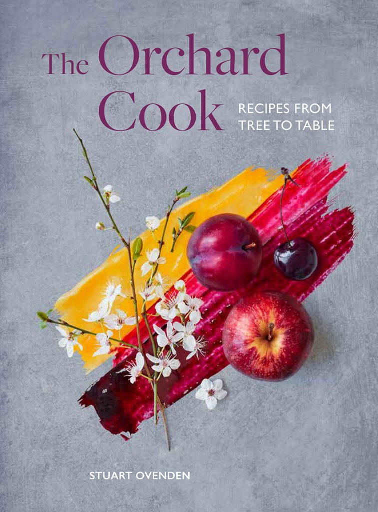 The cover of the cookbook 'The Orchard Cook' by Stuart Ovenden featuring a photograph of blossom and food on a slate background.