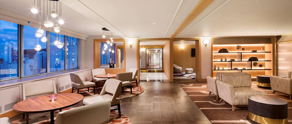 A photograph of the gold lounge at Fairmont The Queen Elizabeth, showing tables and a reading area with sofas.