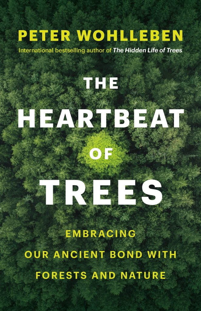 The cover of the book 'The Heartbeat of Trees' by Peter Wohlleben showing yellow and white text over a background aerial image of a forest.