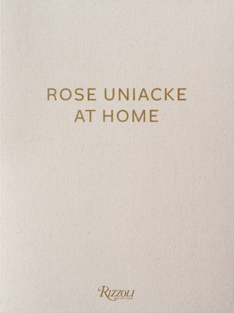 The cover of the book 'Rose Uniacke at Home' by Rose Uniacke featuring bronze text on a beige background.