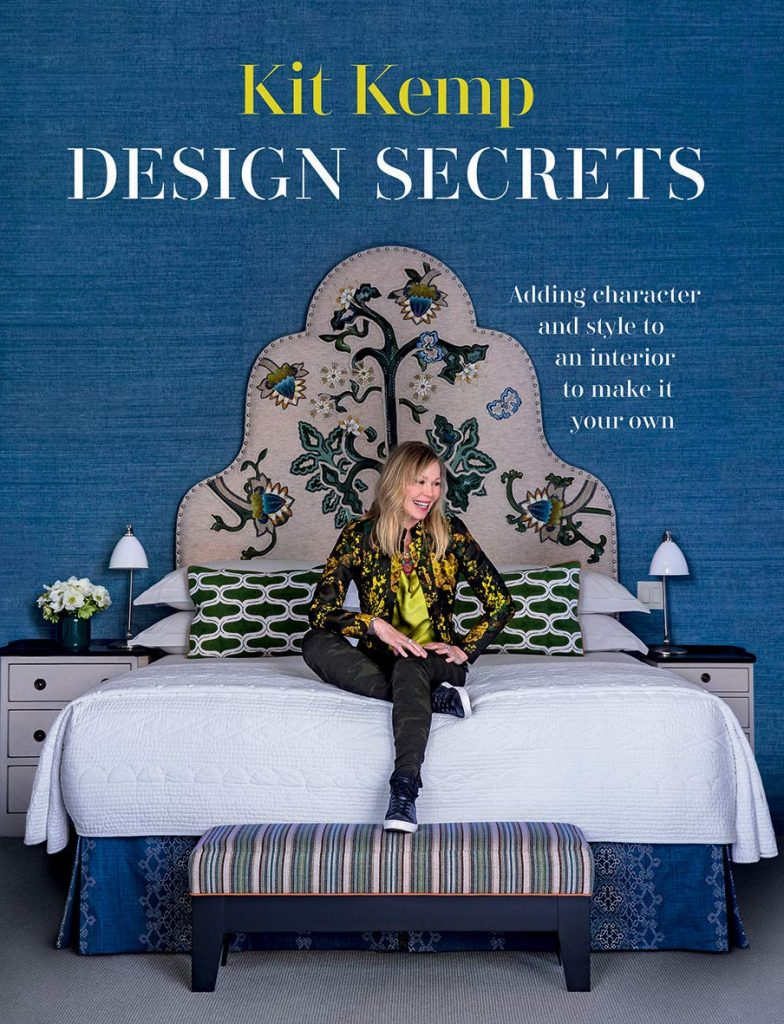 The cover of the book 'Design Secrets' by Kit Kemp featuring white text on a background image of Kemp sitting on a bed.