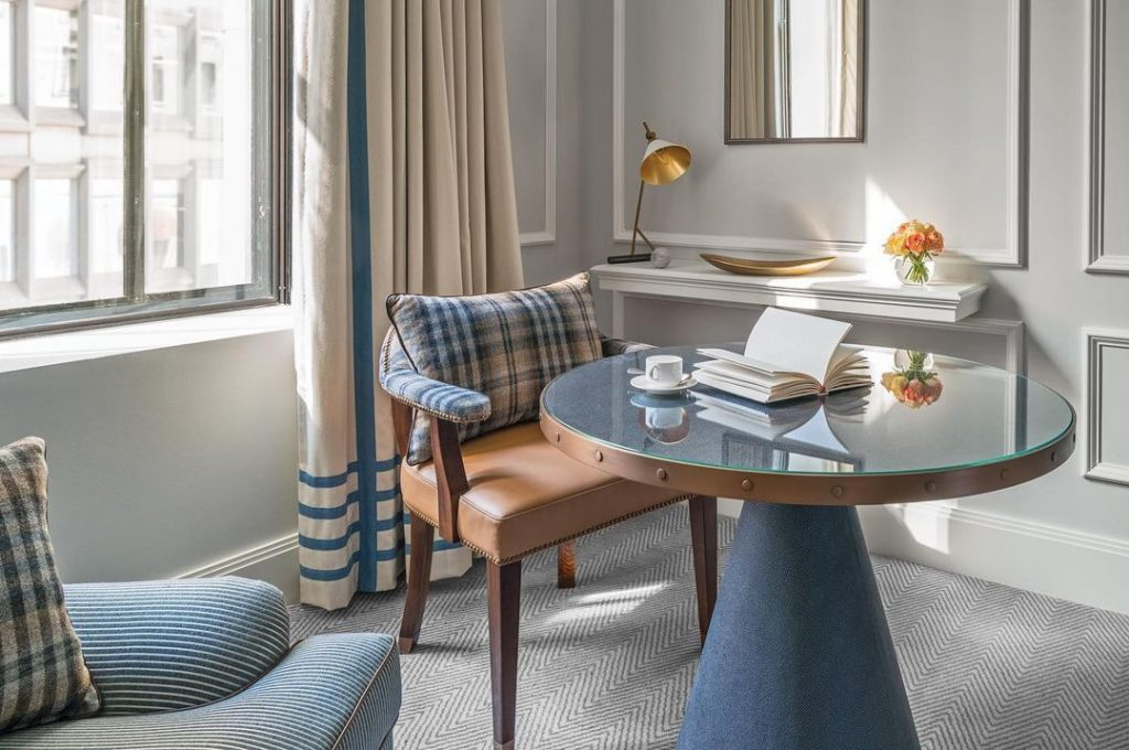 A photograph of an open book on a table in a suite at The Langham.