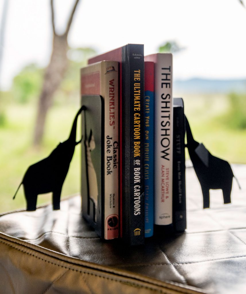 A photograph of a collection of books held up by metal elephant bookends.