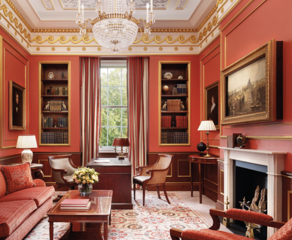 A photograph of the Royal Suite at The Lanesborough Hotel in London. It has red walls and furniture and book shelves on the far wall.