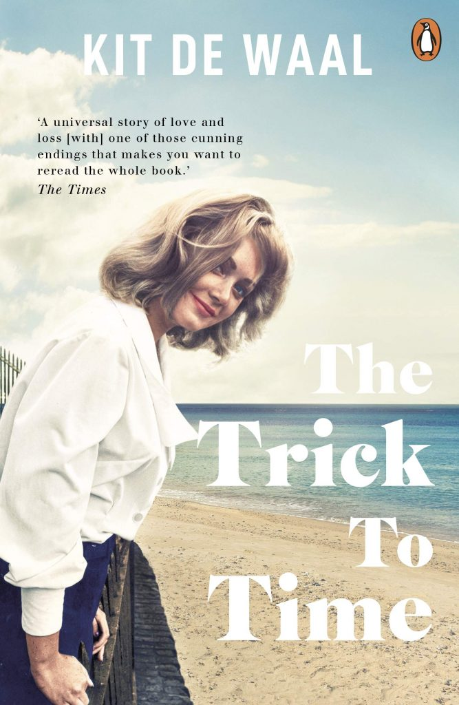 The cover of the book 'The Trick To Time' featuring white text over an image of a woman on a beach.